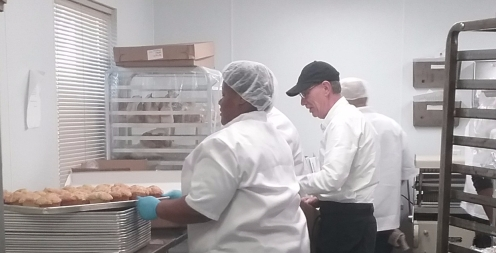 Baker David and Jewell getting the quick breads out of the pan to cool before packaging.